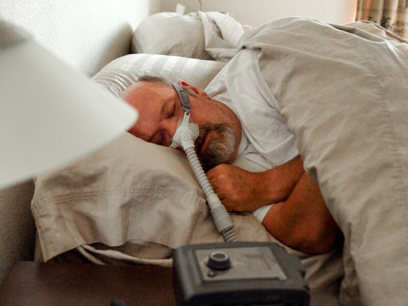 Man with sleep apnea wearing a CPAP (Continuous positive airway pressure) machine