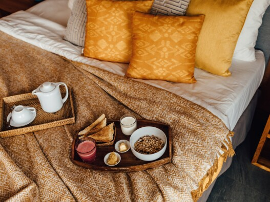Breakfast trays and food on top of comfy yellow bedding