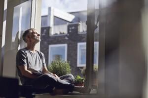 Man sitting by open window, breathing fresh air