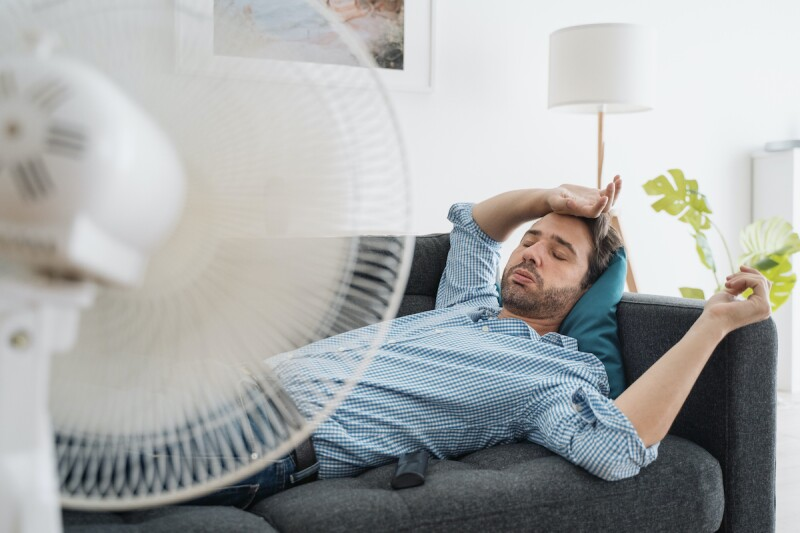 Man trying to cool down in front of a fan during a heat wave