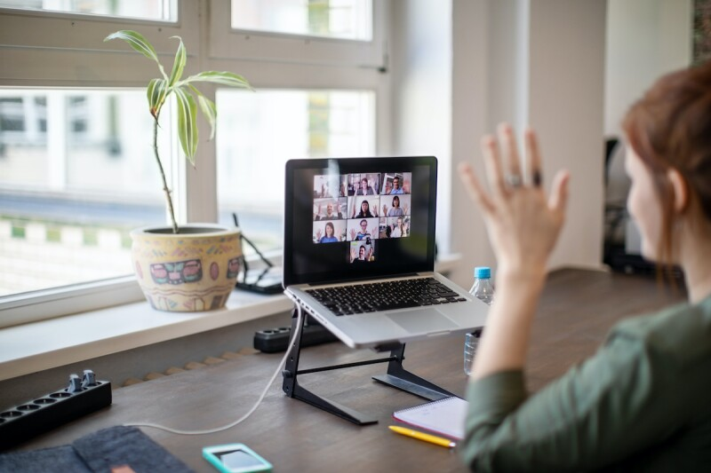 Person using a laptop to have a video meeting at home.