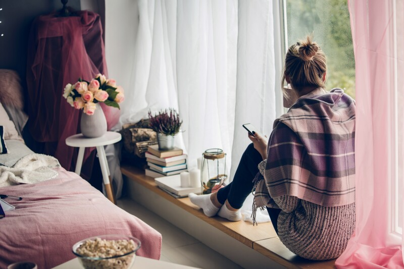 Rear view of young woman sitting next to the window in her bedroom and looking outside while waiting for her friend to respond on her message on smart phone, and also enjoying a sip of coffee.