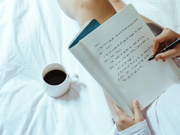 Person writing in a journal with a cup of coffee on their bed