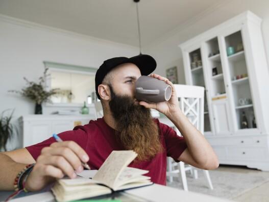 Man with beard drinking coffee and writing in his sleep diary