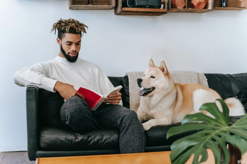 Man reading book with dog beside him