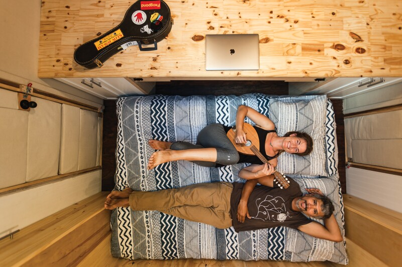 Two people in a van bed playing an instrument