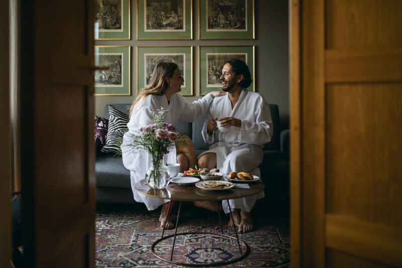Happy couple in bathrobes, sitting in a fancy hotel, enjoying room service on their vacation
