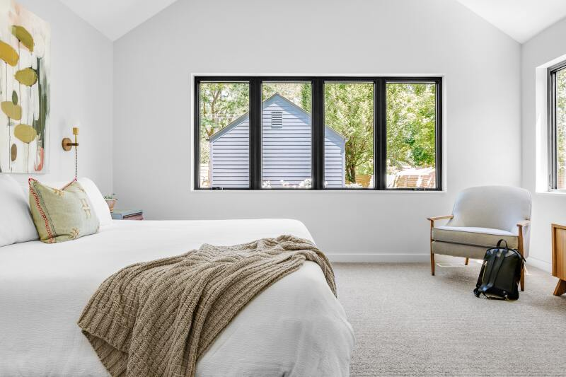 Clean windows in a bright, white bedroom.