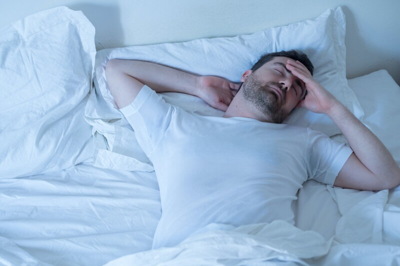 Man shifting in his bed, tossing and turning at night