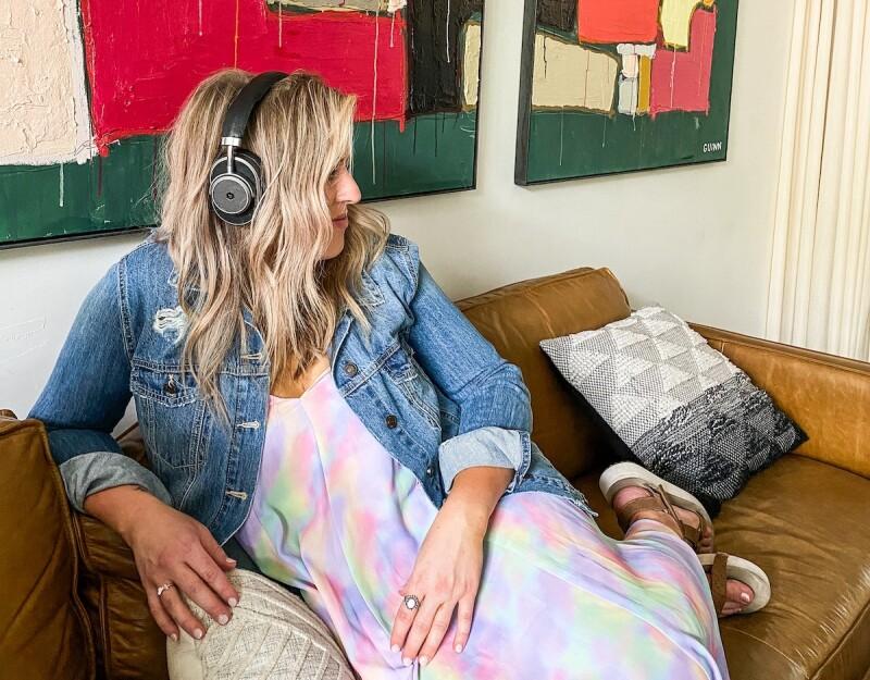 Woman in a tie dye dress with headphones on.