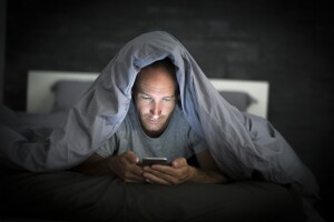 Man on his phone with covers over his head in a dark room