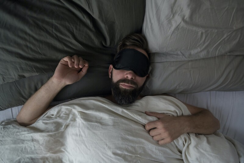 Person wearing eye mask to prevent light disturbance from waking them up in the middle of the night