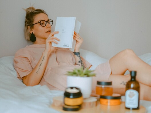 Woman reading a book in bed as part of her bedtime routine.