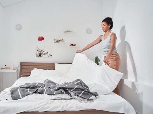 woman changing sheets and bedding