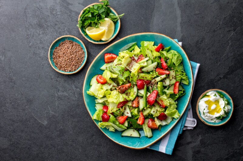 Lettuce salad with tomatoes, cucumbers, and strawberries with dressing on the side