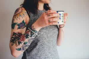 Woman with tattoos holding cup of coffee