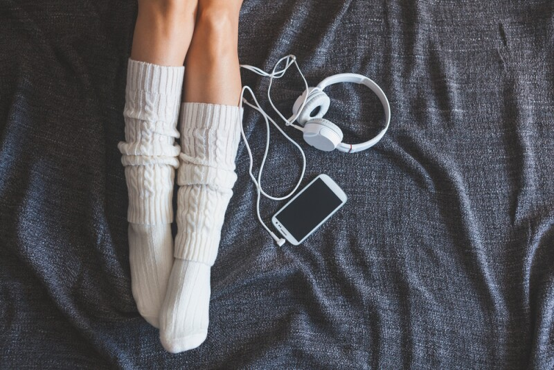 Feet on bed with white headphones and phone.