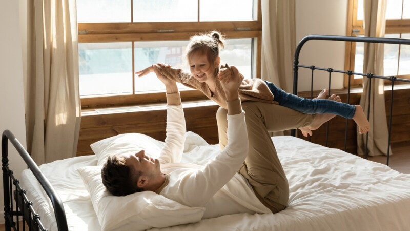Father on a new orthopedic mattress, pretending to be an airplane while playing with his daughter