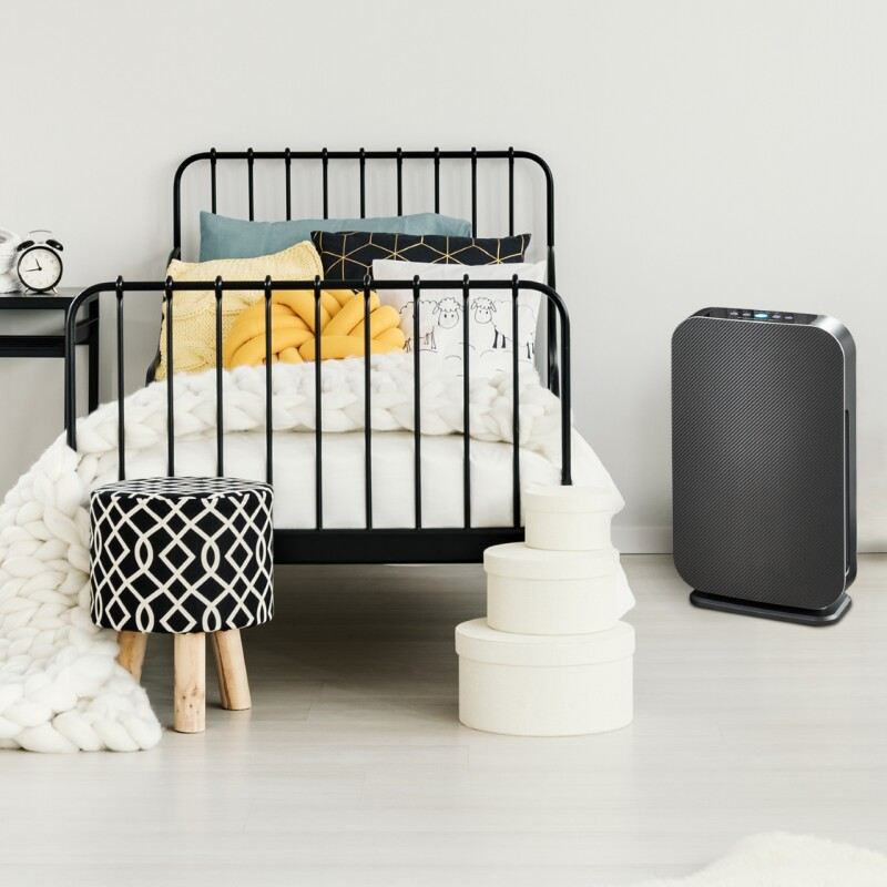 bedroom with cozy bed and Alen air purifier