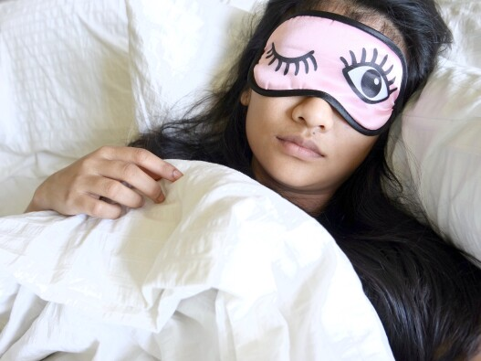 Woman in bed wearing an eyemask