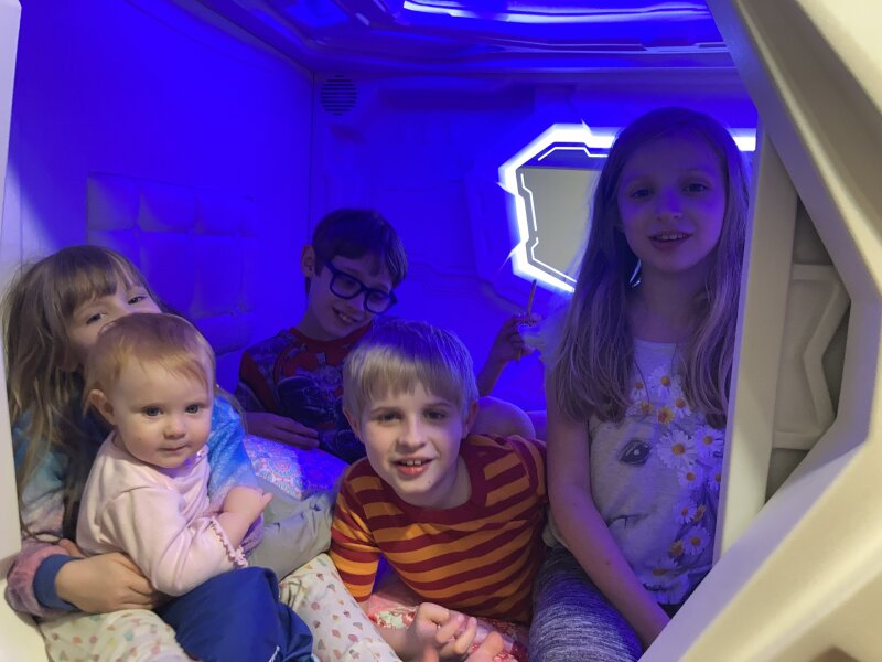 Five siblings inside a zPod, an enclosed capsule bed for autistic children