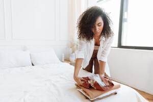 Woman folding laundry on clean bed