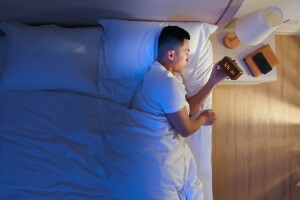 man awake in bed at 3am holding his alarm clock