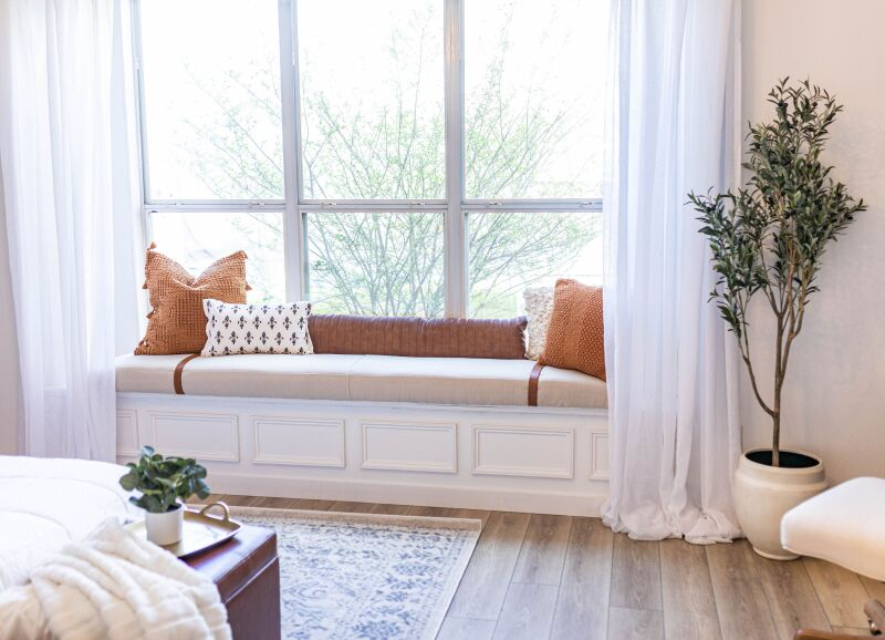 A DIY window sill bench with neutral colors, looking out to a backyard.