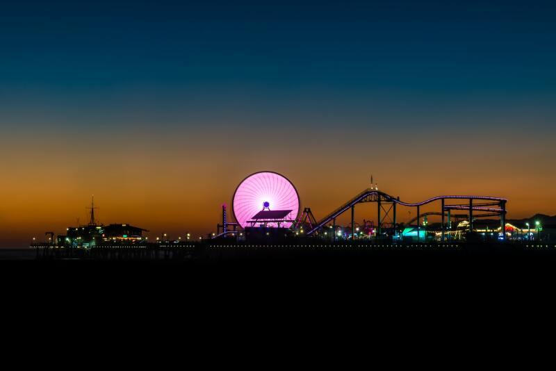 Long exposure shot of a pink ferris wheel at night, in an amusement park
