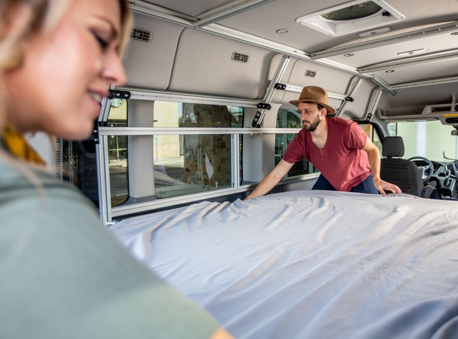 Man and a woman make their camper van bed.