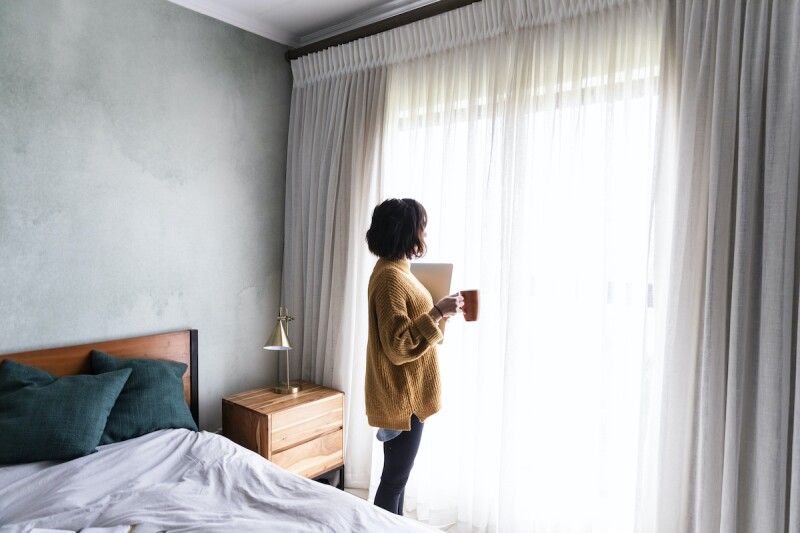 Person in cozy sweater holding a laptop and coffee mug while looking outside the window of their bedroom