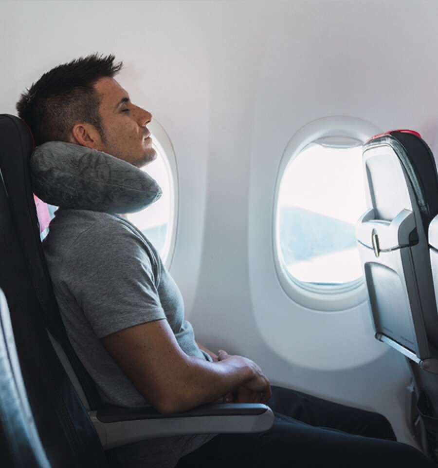 Man sleeping on the plane with a neck pillow and windows open