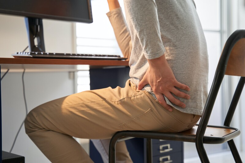 Person clutching their hip while sitting at a work desk