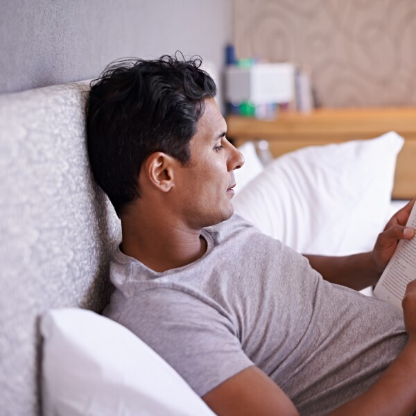 Man in bed practicing good sleep hygiene by reading a paper book.