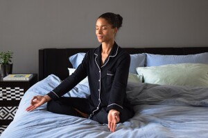 Yoga and Pilates instructor, Alexa Idama, in a calm seated pose, in her bed.