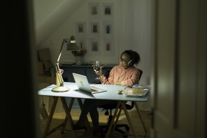Woman drinking wine on a zoom chat and to engage in revenge bedtime procrastination