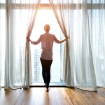 Woman opening curtains and looking out to a bright day