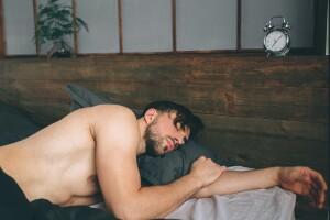 Man sleeping naked in bed